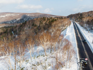Oblique view of a road between Otaru and Niseko during early winter morning with sunlight making the hill side golden