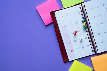 close up of calendar on the purple table, planning for business meeting or travel planning concept