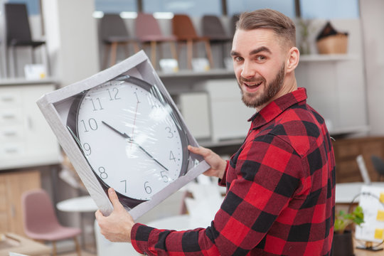 Handsome bearded man looking excited, holding big wall clock. Attractive young man shopping for home goods and decor