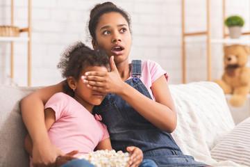 Afraid african american teenage girl closing her sisters eyes