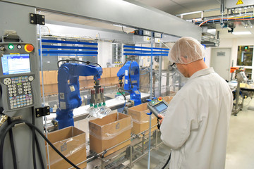 medical products manufacturing in a modern factory - worker operates modern industrial plant