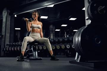 Female bodybuilder training with dumbbells.