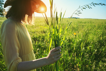 Pretty woman with hat holding grass herb bouquet in summer field