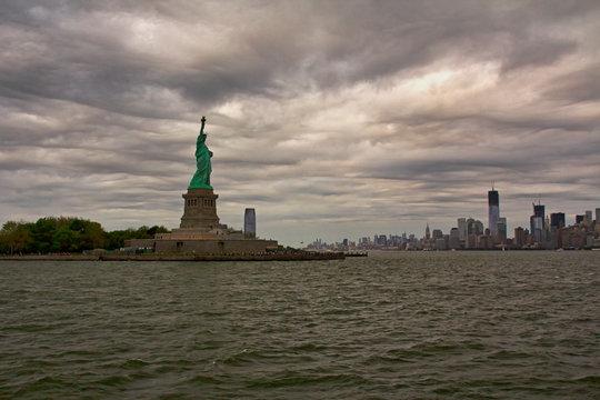 Freiheitsstatue mit Blick auf New York Skyline, bewölkter Himmel