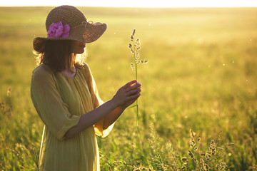 Pretty woman with hat holding grass plant in summer field