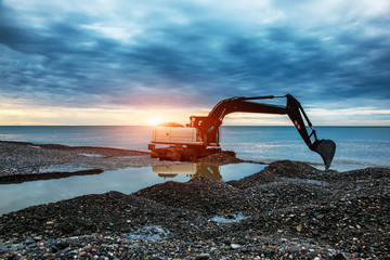 backhoe or digger working with bucket at industrial earth excavation site near sea in sunrise light