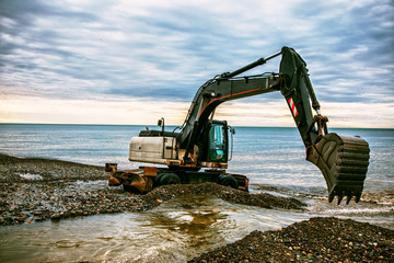 backhoe or digger working with bucket at industrial earth excavation site near sea