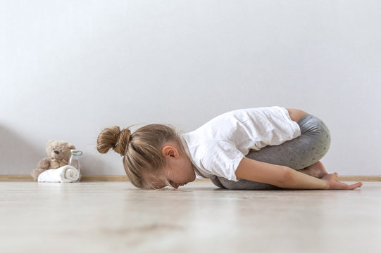 A little cute girl practices a yoga pose indoors. The child does yoga and gymnastic exercises.