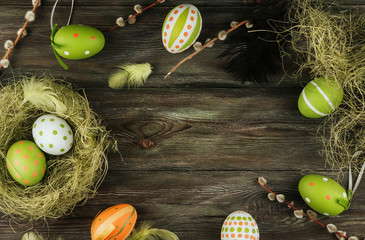 Green and orange Easter eggs in a sisal nest on an old wooden background. Bird feathers. Painted eggs. Easter decoration.