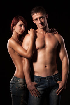 Front view of beautiful young couple posing topless. Attractive lady wrapping arm around shoulders of handsome man with naked torso. Isolated on black studio background. Concept of love and sexiness.
