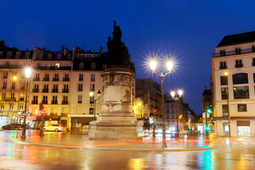 Place de Clichy at rainy night , Paris. Bronze statue of Marechal Moncey at the centre of the square. Crossing four districts of the city at one point.
