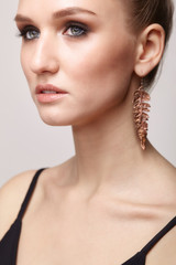 Beautiful woman with galvanic earring in form of leaf