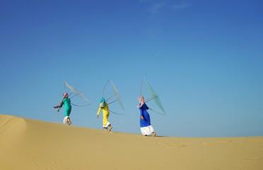 Beautiful photo of Cham's girls on the way back home on Nam Cuong sandy dune in dawn, Phan Rang, Ninh Thuan province, Vietnam