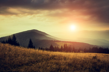 Beautiful landscape in the mountains at sunrise with haze and cloudy sky. View of the magnificent natural scenery of mountains hills. Filtered image: cross processed retro effect.