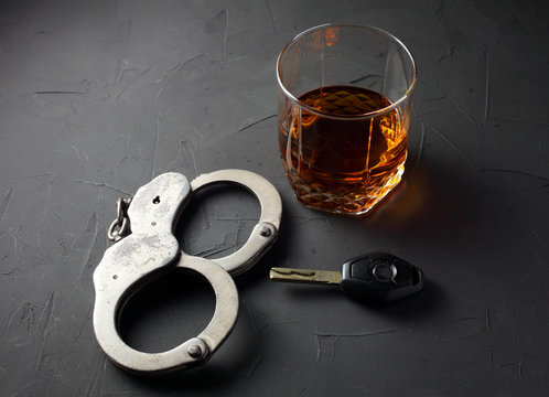 concept of criminal liability for driving while intoxicated. Bakal with cognac, handcuffs, car key on a dark background.