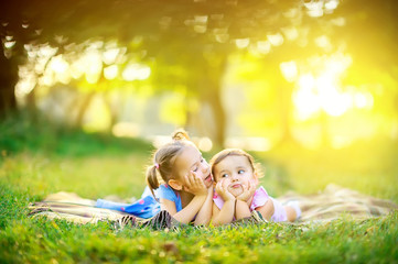 Cute children play in the park at sunset. Girls are lying on the grass playing and having fun. Children play and have fun outdoors.