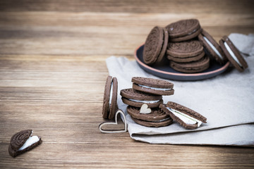 chocolate cookie sandwich in a clay plate on Kraft paper on a wooden background. wooden hearts. happy Valentine's day. beautiful picture with biscuits. texture.