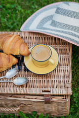 Breakfast on the grass. Cup of coffee and French croissants