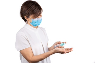 Asian woman with face mask applying sanitizer onto hand for protection against virus germs