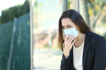 Infected woman wearing a mask coughing in a bus stop