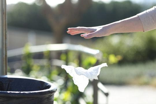 Hand throwing litter outside a bin in a park