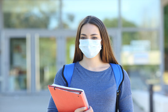 Student wearing a mask walking in a campus