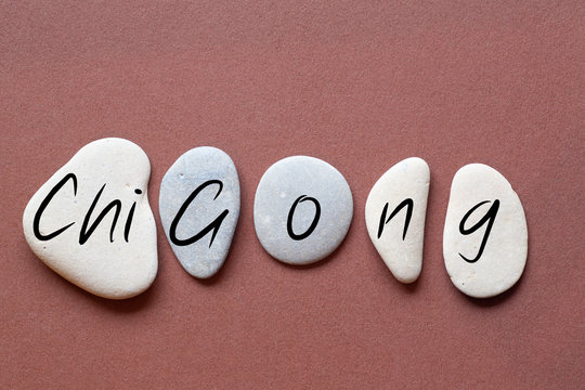 Chi Gong as a word on flat stones in natural color and shape. A letter in black color on each stone isolated against a brown background
