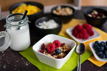 Schüssel mit leckeren Müsli. Dazu Kokosmilch im Einmachglas und Zutaten für das Müsli