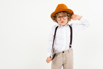 Beautiful boy with curly hair in white shirt, brown hat, glasses with black suspenders stands isolated on white background