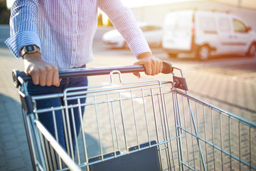 Going to the market. Woman hand hold supermarket shopping cart. Young modern woman standing infront of a supermarket after shopping.