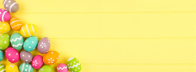 Wall Mural - Colorful Easter banner with Easter Egg corner border against a yellow wood background. Top view with copy space.