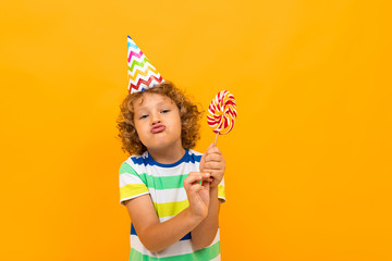 Little boy with curly hair in blue shirt and shorts with big lolipop isolated on yellow background