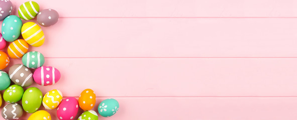 Wall Mural - Colorful Easter banner with Easter Egg corner border against a pink wood background. Overhead view with copy space.