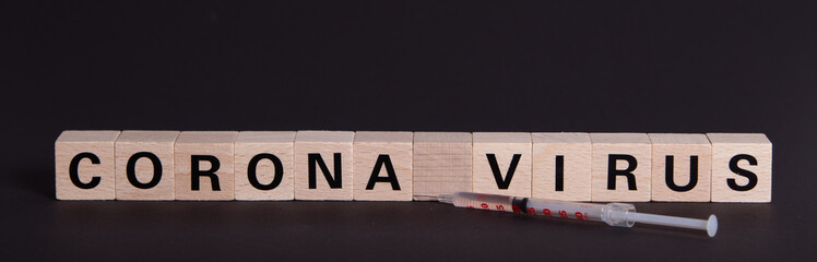 wooden cubes with text coronavirus and a syringe, vaccine, black background