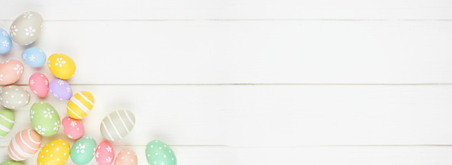 Wall Mural - Pastel colored Easter Egg banner with corner border against a white wood background. Overhead view with copy space.