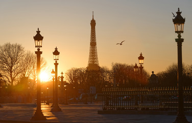 Silhouettes of the Eiffel Tower, street lamps of Concorde square at sunset Paris.