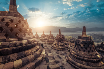 Amazing view of stone stupas at ancient Borobudur Buddhist temple against beautiful landscape on background. Great religious architecture. Magelang, Central Java, Indonesia Fotomurales