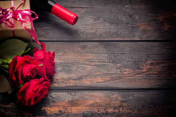 Valentines day romantic greeting card. Red rose flowers, wine bottle and gift box on wooden table. Free space.