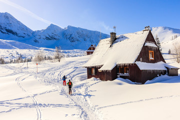 Two skiers walking past mountain hut in beautiful Gasienicowa valley in winter time, Tatra Mountains, Poland