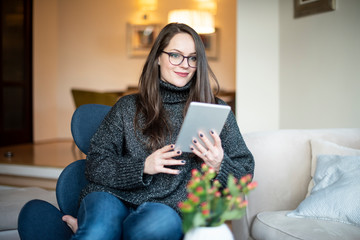 Young woman using digital tablet while relaxing in the armchair at home