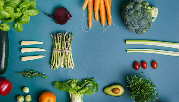 Top view set of healthy raw vegetables and fruits with copy space on the classic blue background. Vegetarian and vegan diet. Veganism. Sustainable lifestyle, good, plant-based foods. Wide banner.