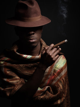An African man in a hat and a poncho smokes a cigar. Studio shooting. The dark background.