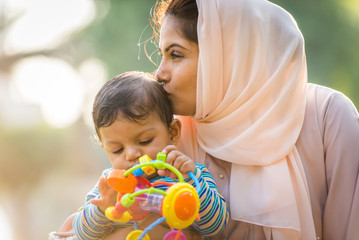 Arabic mom and her little toddler playing outdoors