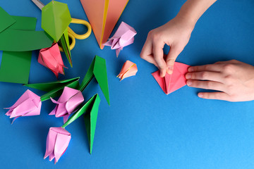 Mother's day gift. Hands of a child. Mother's Day, happy birthday, March 8, Women's Day, Valentine's Day. Bouquet of tulips from origami colored paper on a blue background. copy space.