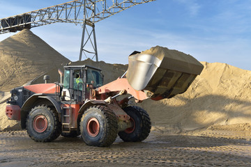 Gravel pit: building and wheel loader loading gravel onto a truck