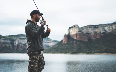 fisherman enjoy hobby with fishing rod on lake, person catch fish on background mountain, holiday relaxation fishery concept