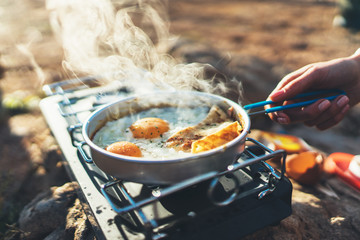 person cooking fried eggs in nature camping outdoor, cooker prepare scrambled breakfast picnic on metal gas stove, tourism recreation outside; campsite lifestyle
