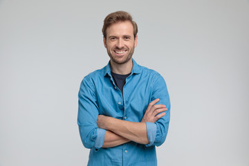 Fototapeta enthusiastic young casual man crossing arms and smiling