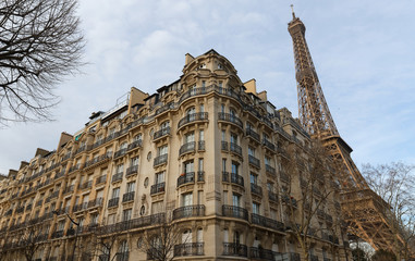 Traditional French house with typical balconies and windows and Eiffel tower in the background . Paris.