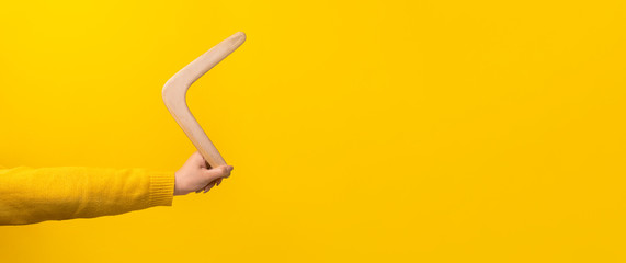 boomerang in female hand over yellow background, panoramic mock-up